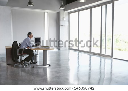 Full length side view of a man sitting at desk in empty office