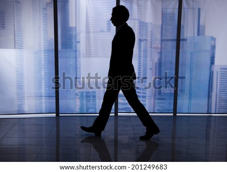 Full length side view of businessman walking by office window with city view in background
