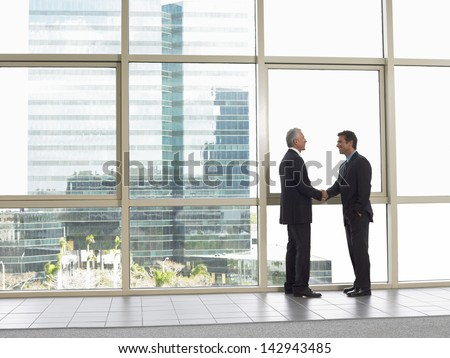 Full length side view of businessmen shaking hands in office building