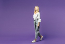 Full length side view of cheerful beautiful elderly gray-haired blonde woman lady 40s 50s in white dotted blouse walking going looking aside isolated on bright violet color background studio portrait