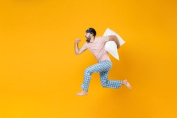 Full length side view of excited cheerful young man in pajamas home wear sleep mask jumping like running hold pillow isolated on yellow background studio portrait. Relax good mood lifestyle concept