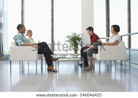 Full length side view of four business people sitting in modern waiting room at office