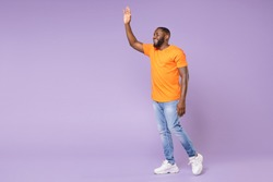 Full length side view of joyful young african american man wearing basic casual orange t-shirt waving and greeting with hand as notices someone isolated on pastel violet background, studio portrait