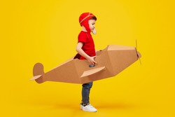 Full length side view of little boy in pilot hat imitating engine sound while playing with cardboard aircraft against yellow background