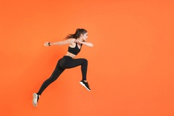 Full length side view of portrait of young fitness sporty woman 20s wearing black sportswear posing training working out jumping like running looking aside isolated on orange color background studio