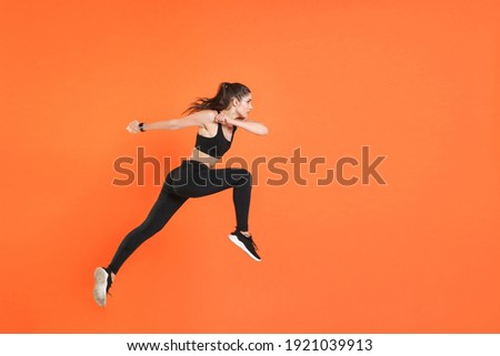 Full length side view of portrait of young fitness sporty woman 20s wearing black sportswear posing training working out jumping like running looking aside isolated on orange color background studio Photo stock ©