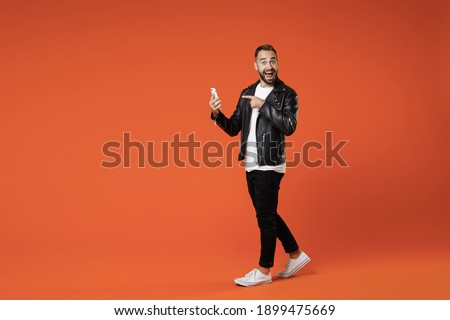 Full length side view of shocked young bearded man in basic white t-shirt black leather jacket standing pointing index finger on mobile cell phone isolated on orange colour background studio portrait