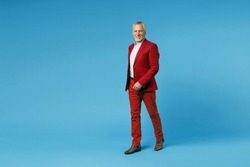 Full length side view of smiling cheerful elderly gray-haired mustache bearded business man wearing red jacket suit walking going looking camera isolated on blue color background studio portrait