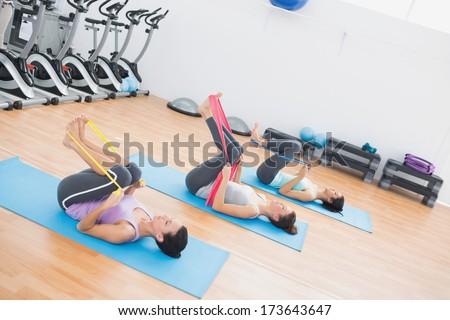 Full length side view of sporty young women with exercise bands in the fitness studio