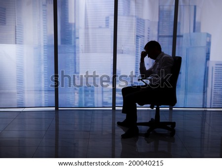 Full length side view of tensed businessman sitting on chair by office window