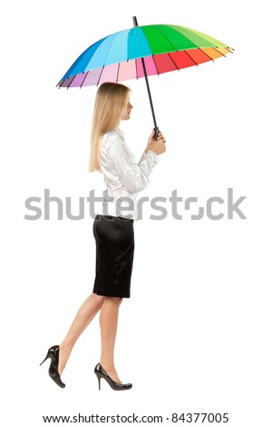 Full length, side view of young business woman holding an umbrella over white background