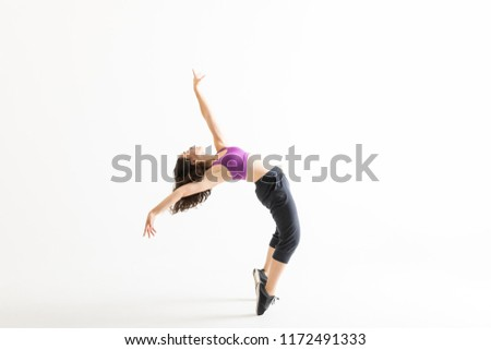 Full length side view of young jazz dancer on tiptoes bending backward on white background