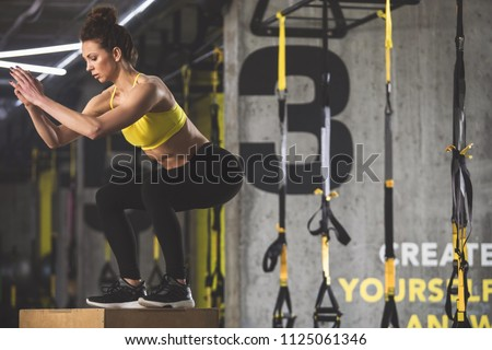 Full length side view orderly girl gesticulating hands while crouching in keep-fit studio