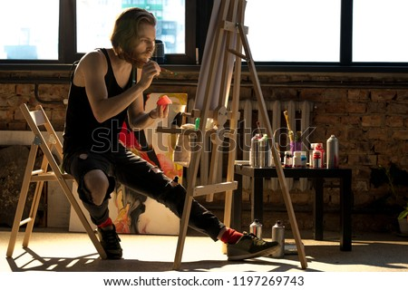 Full length side view portrait of handsome male artist painting on easel while enjoying work in art studio lit by sunlight, copy space