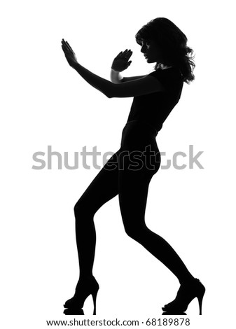 full length silhouette in shadow of a young woman fight karate  self defense  in studio on white background isolated