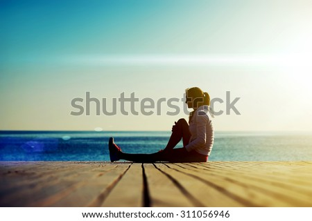 Full length silhouette of young woman runner sitting on the wooden pier against ocean while resting after an run in beautiful evening, sportswoman with good figure resting after an active run outdoors