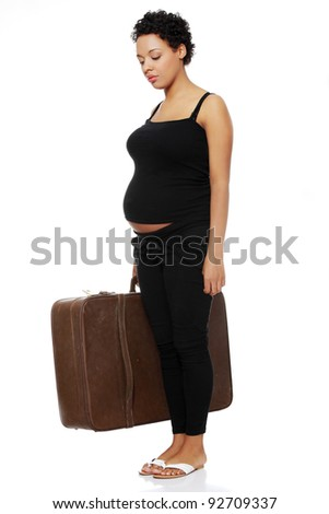 Full length site view of a sad pregnant woman holding a case.