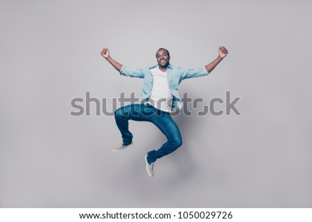 Full length, size portrait of confident attractive, joyful, cheerful, positive, glad guy in shirt, sneakers jumping with raised fists, looking at camera, isolated on grey background #1050029726