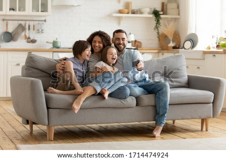 Full length smiling father holding cellphone, making selfie shot, recording video with happy wife and little kids siblings. Excited parents looking at mobile screen with kids, feeling excited.