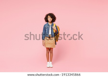 Full length smiling little african american kid school girl 12-13 year old in casual denim clothes with backpack stand isolated on pastel pink background studio portrait. Childhood education concept. Foto stock ©