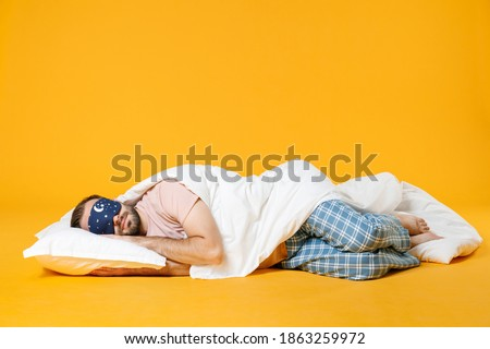 Full length smiling pretty young bearded man in pajamas home wear sleep mask lying with pillow blanket isolated on bright yellow colour background studio portrait. Relax good mood lifestyle concept