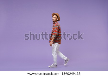 Full length smiling young african american man in casual colorful shirt hat walking step look camera isolated on violet background studio portrait. People emotions lifestyle concept. Mockup copy space Stock photo ©