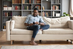 Full length smiling young african ethnicity man sitting on comfy couch, playing online mobile game. Happy mixed race guy looking at smartphone screen, reading pleasant message news, relaxing at home.