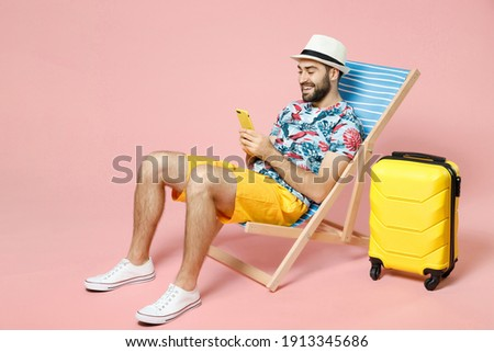 Full length smiling young traveler tourist man in hat sit on deck chair using mobile cell phone typing sms message isolated on pink background. Passenger travel on weekend. Air flight journey concept
