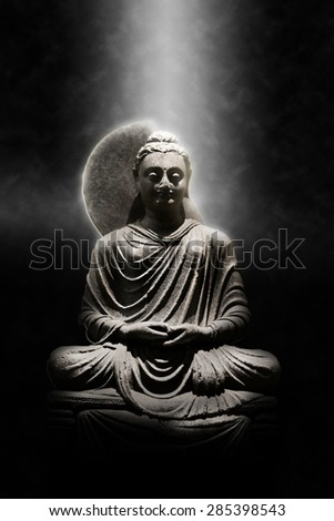 Full Length Stone Carved Seated Buddha Statue Dramatically Lit from Above on Dark Background, Meditation and Spirituality Concept Still Life Image