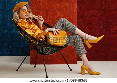 Full-length studio fashion portrait of elegant woman wearing yellow color sunglasses, beret, silk blouse, houndstooth printed trousers, pointed toe shoes, posing on chair, holding stylish leather bag