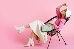 Full-length studio fashion portrait of young elegant happy smiling woman wearing trendy spring outfit: pink blouse, white hat, pleated skirt, ankle boots, holding stylish faux leather bag