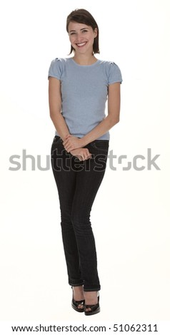 Full length studio photo of pretty young woman standing, smiling, looking at camera. White background.