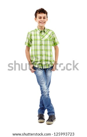 Full length studio portrait of a teen boy in green plaid shirt with hands in his pockets