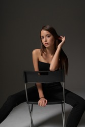 Full length studio portrait of young slim tanned caucasian girl in black jeans and bando top sitting at chair and posing against grey studio background