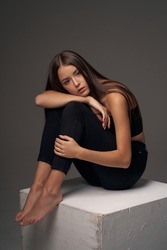 Full length studio portrait of young slim tanned caucasian girl in black jeans and bando top sitting and posing against grey studio background