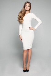 Full length studio shot of gorgeous slim woman with long wavy hair posing in casual white dress and black high heels holding arm on hip and looking at camera. isolate on grey background.