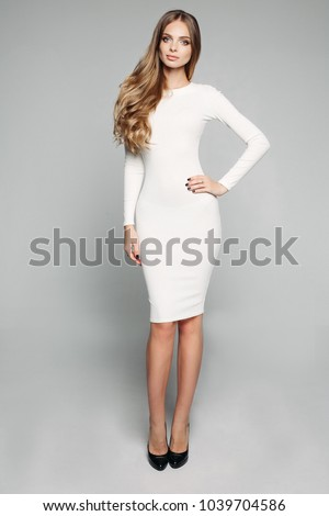 Full length studio shot of gorgeous slim woman with long wavy hair posing in casual white dress and black high heels holding arm on hip and looking at camera. isolate on grey background. #1039704586