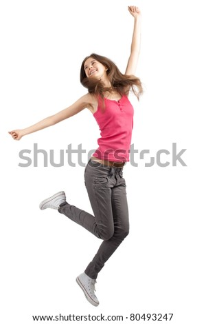 Full length studio shot of happy young woman jumping with arms extended . Over white background