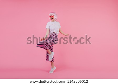 Full-length studio shot of lovely girl dancing in white sneakers. Indoor portrait of pleased caucasian lady in pink peruke and trendy pants. #1142306012