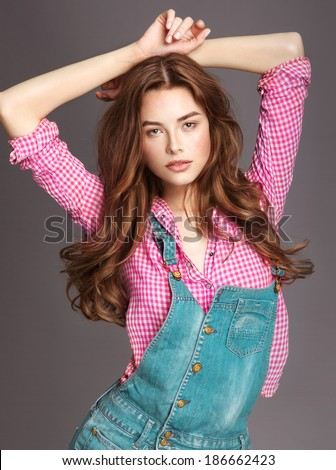 Full length studio shot of pretty model on grey background with long shine hair