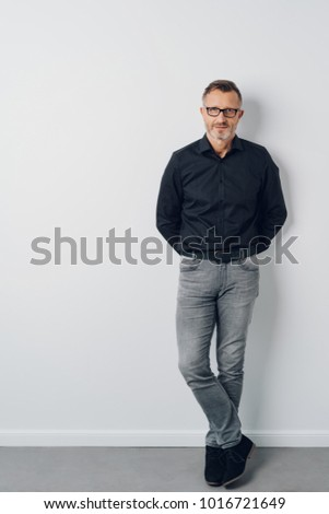 Full length studio shot portrait of a middle-aged confident man wearing cool casual clothes while looking at camera against gray background for copy space