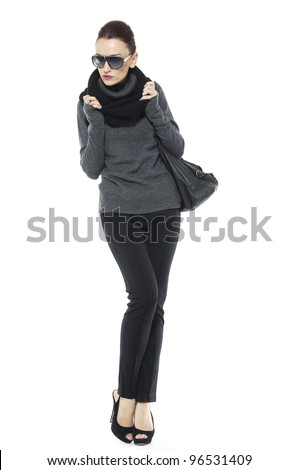 Full length stylish girl in glasses posing with bag. Isolated over white