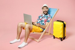 Full length surprised young traveler tourist man in summer clothes hat sit on deck chair work on laptop computer isolated on pink background. Passenger travel on weekend. Air flight journey concept