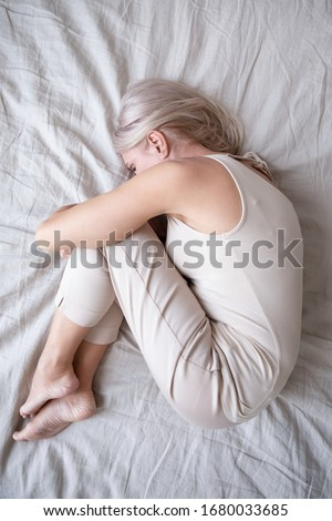 Full length top above view stressed middle aged woman lying on bed in fetal position, embracing knees, suffering from depression or insomnia. Upset mature lady feeling unwell, having health problems.