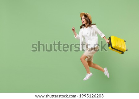 Full length traveler tourist woman in casual clothes straw hat jump high hold suitcase run isolated on pastel green background. Passenger travel abroad on weekends getaway. Air flight journey concept