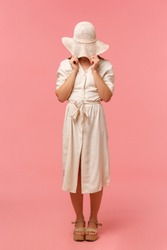 Full-length vertical portrait silly and shy woman standing in dress, hiding her face behind summer hat, standing over pink background, embarassed look, feeling awkward or blushing