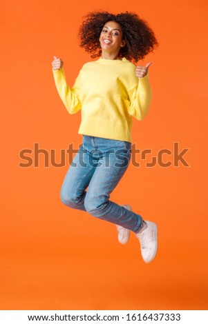 Full-length vertical shot happy and satisfied, carefree joyful african-american woman with afro, curly haircut, jumping from joy and happiness, showing thumbs-up over orange background