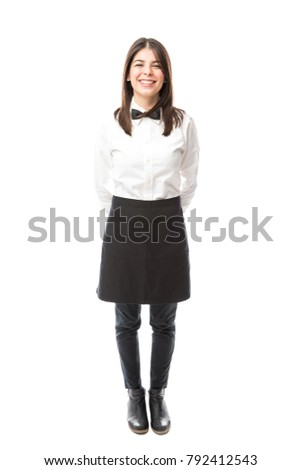 Full length view of a beautiful Hispanic waitress wearing an apron and a bowtie and smiling;