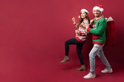 Full length view of a cute cheerful couple walking and carrying a sack with Christmas presents and delivering them