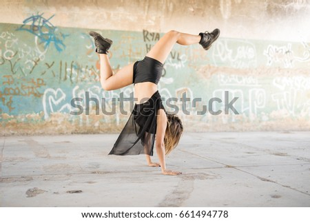 Full length view of a female contempo dancer doing a handstand while performing in an abandoned building